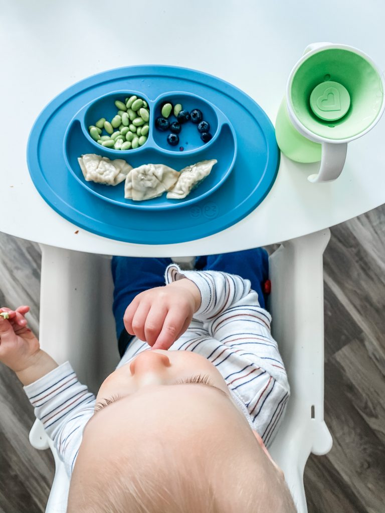 a 16 month old eating dumplings, edamame, and blueberries