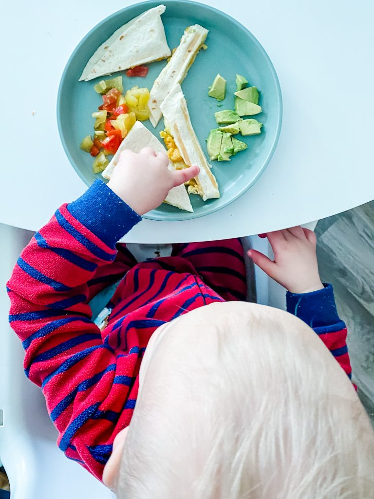 photo of a toddler in a high chair eating a quesadilla, avocado and tomatoes